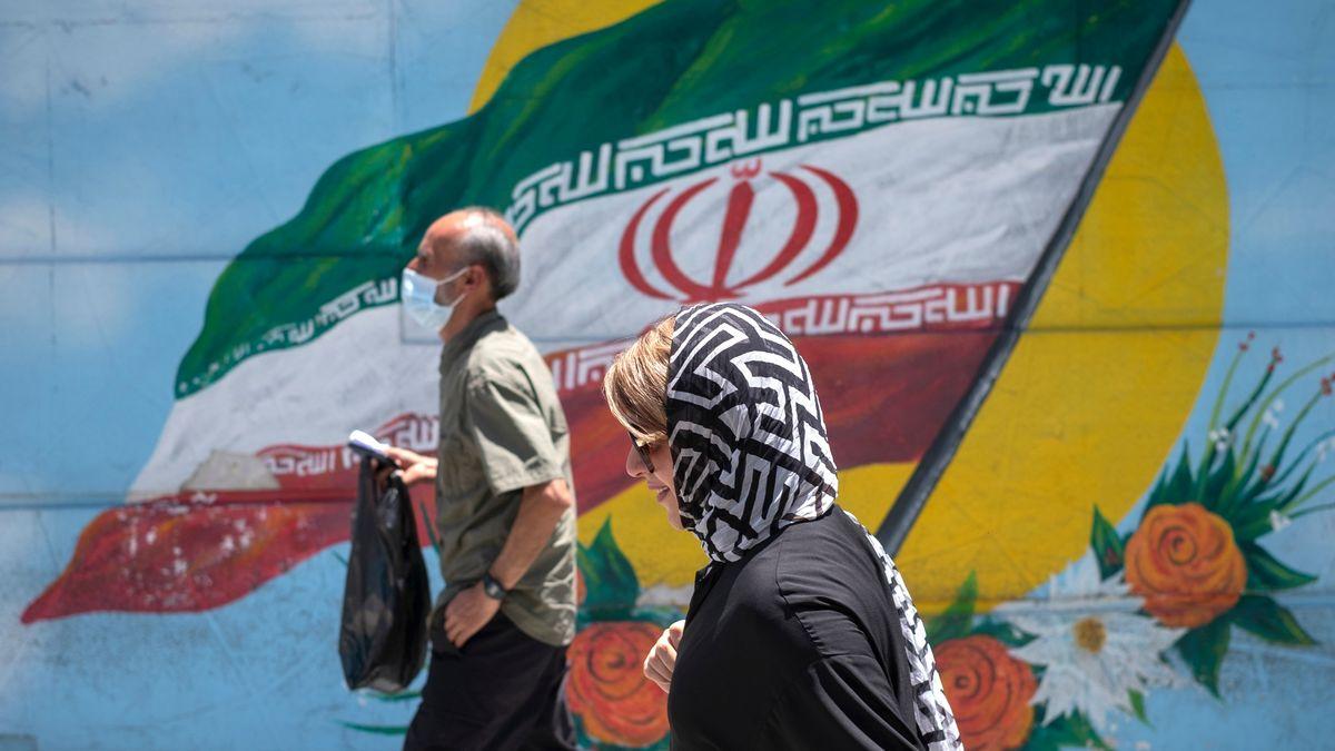 Menschen laufen in Teheran an einer mit der iranischen Nationalflagge bemalten Wand vorbei.
