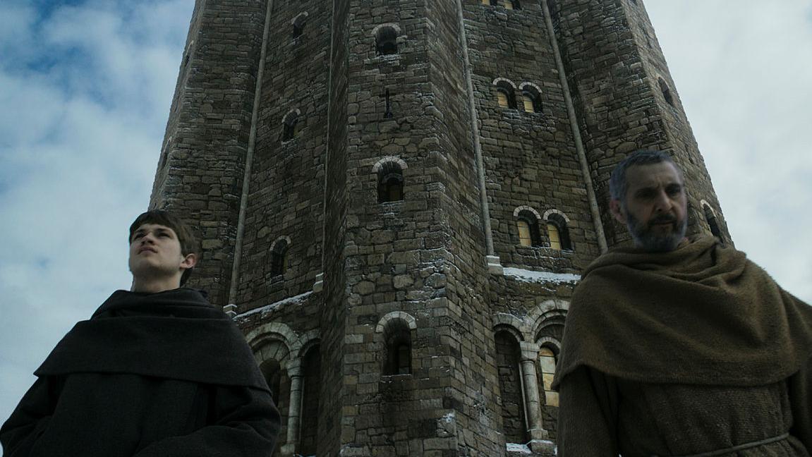 Zwei Mönche stehen vor einem Turm.