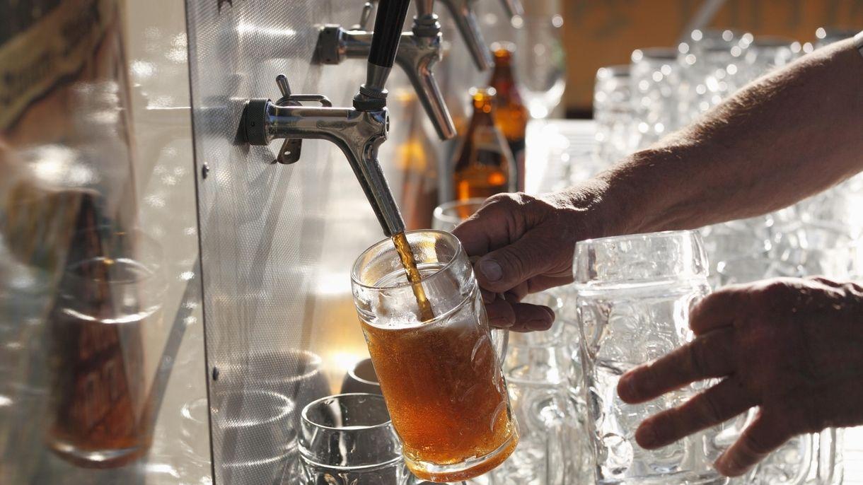 Wirt zapft aus einer Zapfanlage Bier in einen Glaskrug
