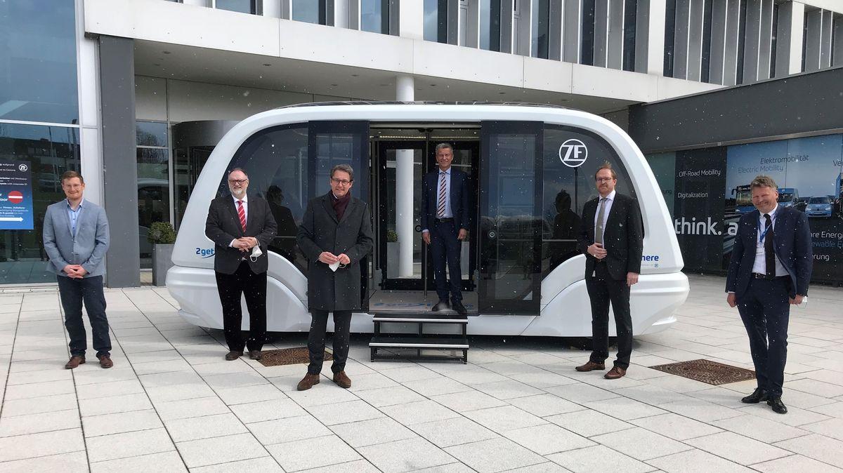 Sechs Männer stehen vor einem autonom fahrenden Bus