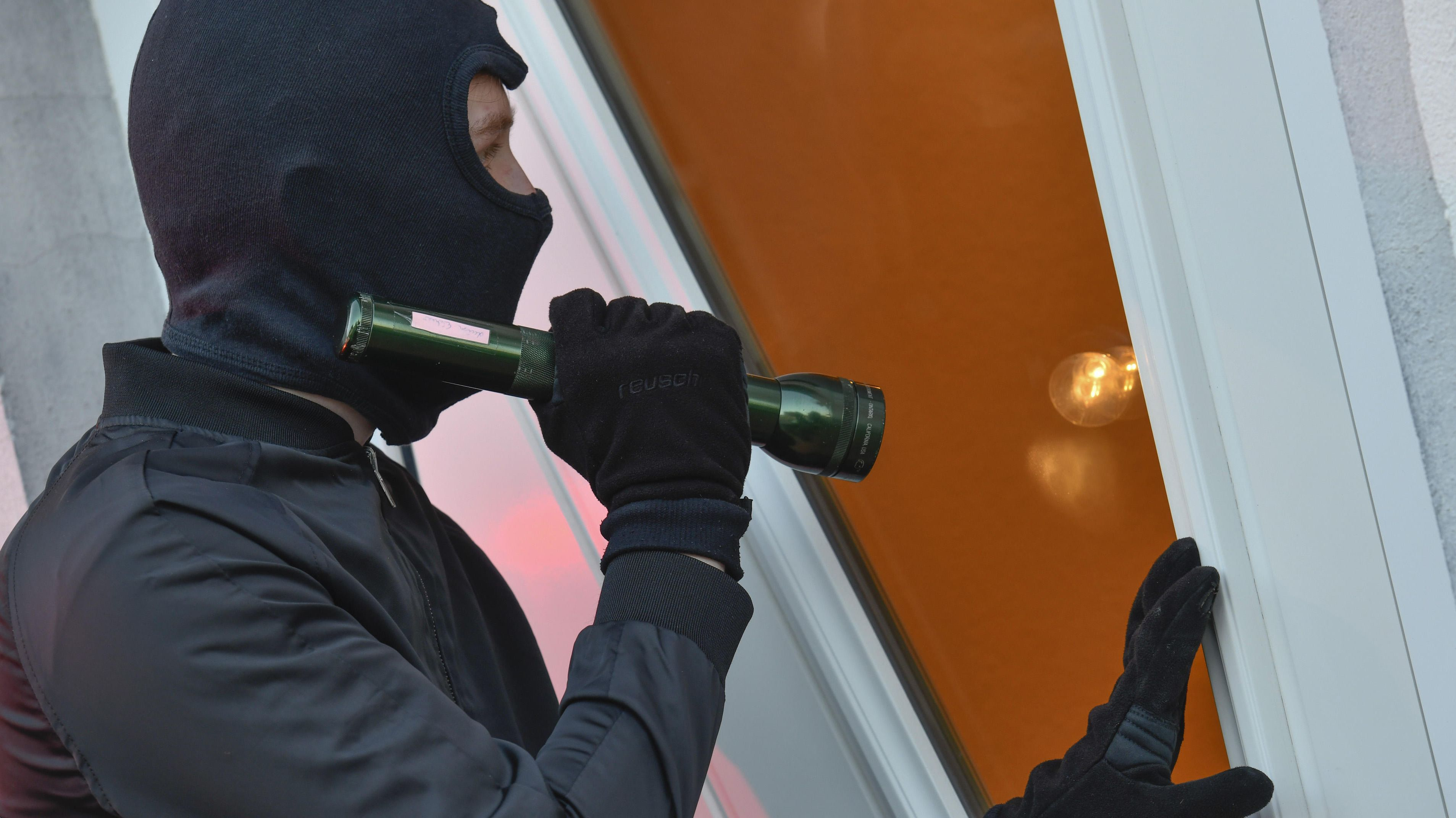 Ein maskierter Mann leuchtet mit einer Taschenlampe in eine Wohnung.