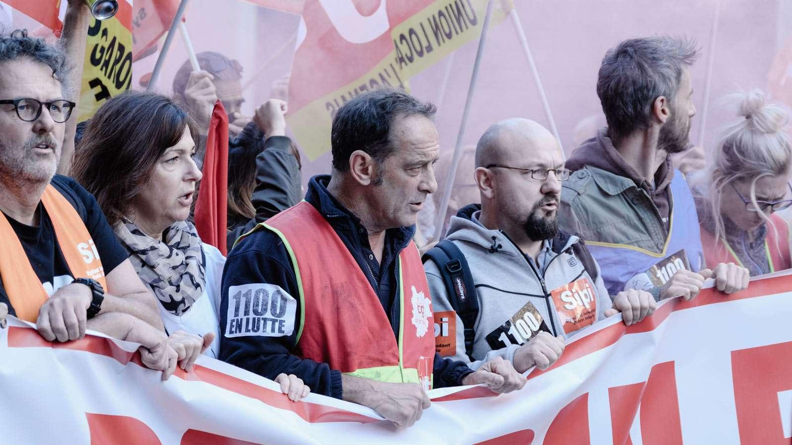 """Streikende Menschen, die hinter einem Spruchband stehen und gegen die Schließung einer Fabrik demonstrieren, Szene aus dem Film """"Streik""""."""