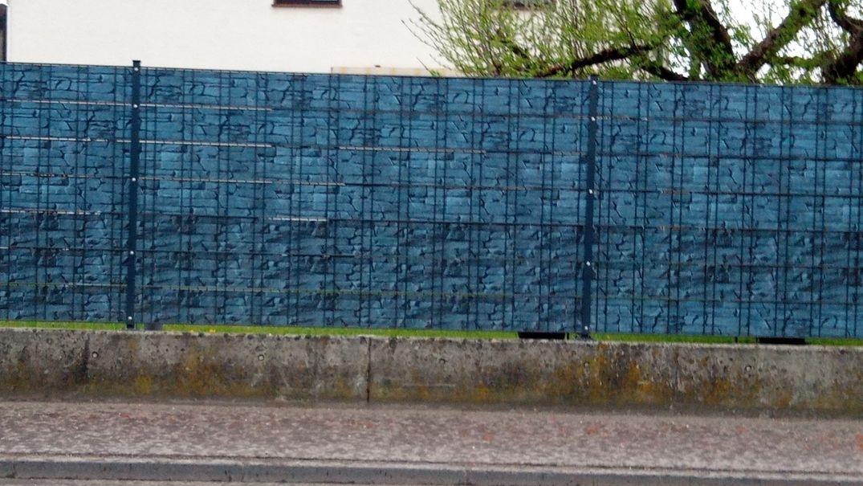 Sichtschutz - Hier ein Blauer Zaun über einer moosbewachsenen Mauer.