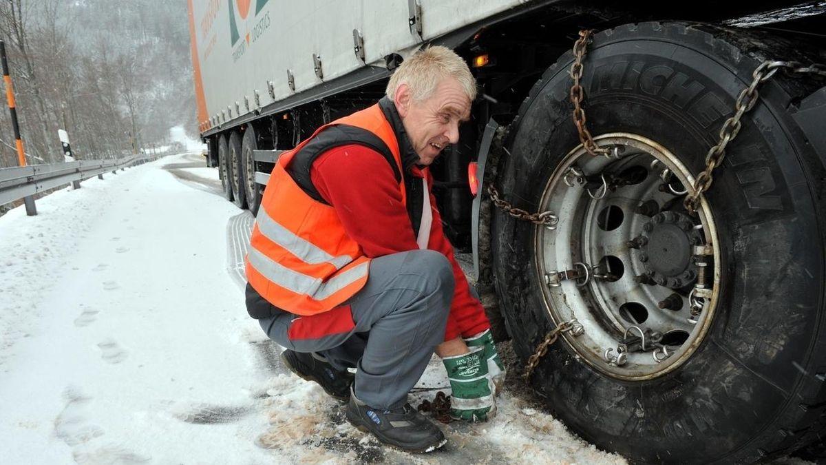 Ein Lastwagen-Fahrer in oranger Warnweste spannt Schneeketten über den Reifen seines Lastwagens, der auf schneebedeckter Fahrbahn steht.