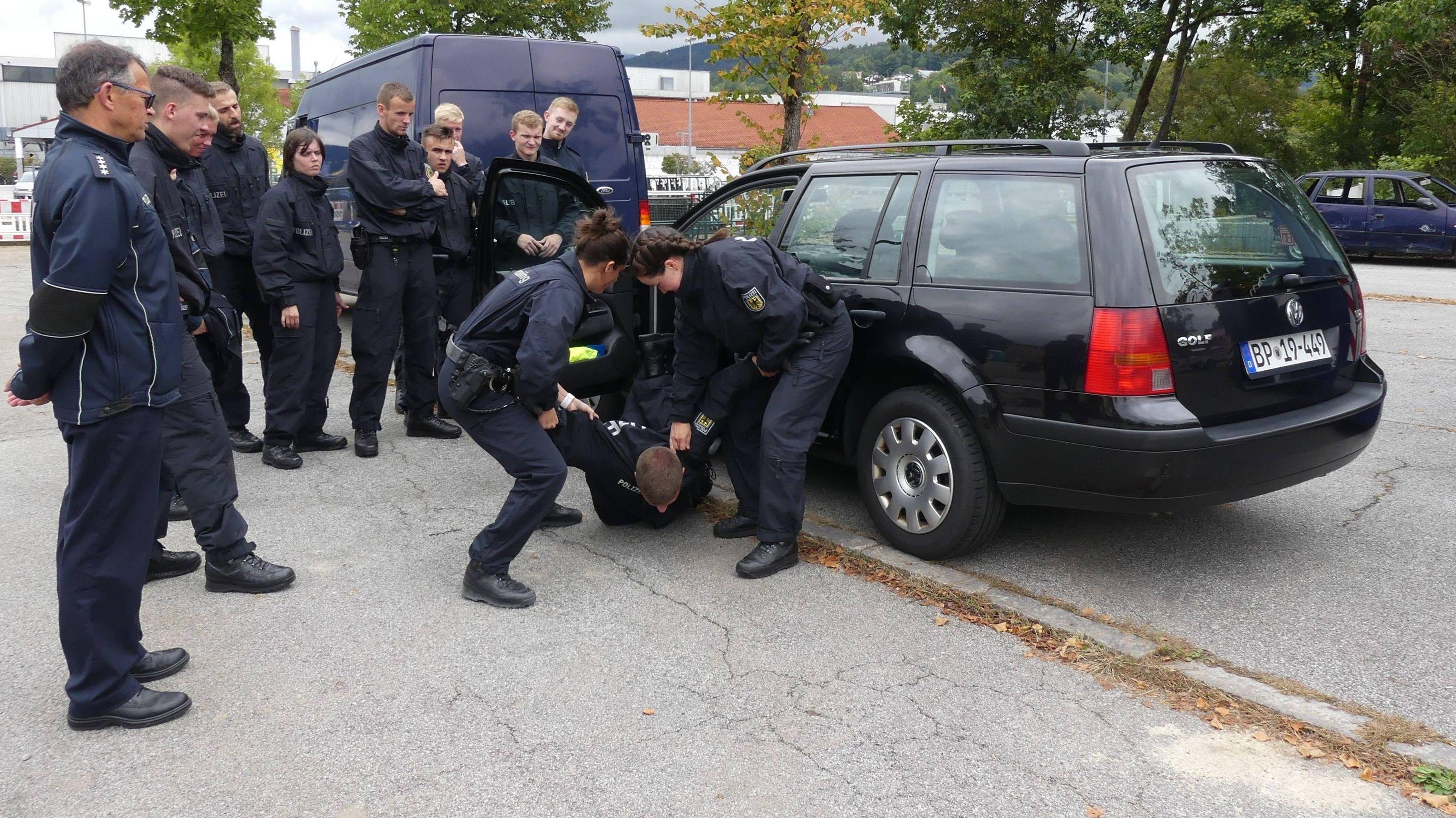 Das Verbringen von renitenten Personen aus Fahrzeugen wird unter dem prüfenden Blick von Polizeihauptkommissar Carsten Berkey  trainiert.