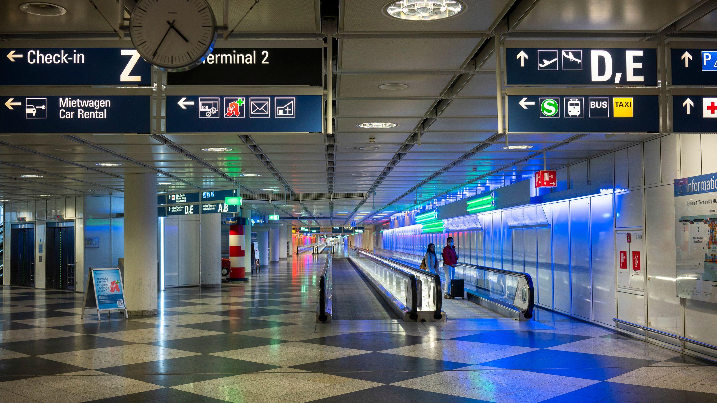 Ein leerer Gang zwischen den Abflughallen am Münchner Flughafen. Auf einem Rollband stehen verloren zwei einzelne Menschen.