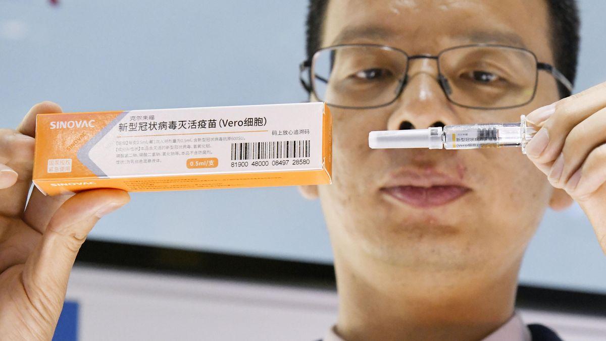 Ein Forscher des chinesischen Pharmakonzerns Sinovac hält den Impfstoff in der Testphase vor sich.