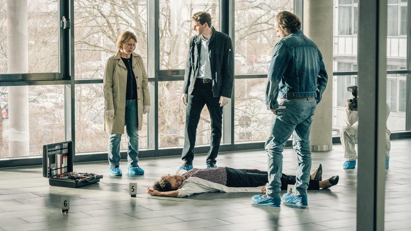 Die drei Ermittler des Franken-Tatorts stehen in einem Gebäude der Universität Bayreuth um eine tote Frau herum.
