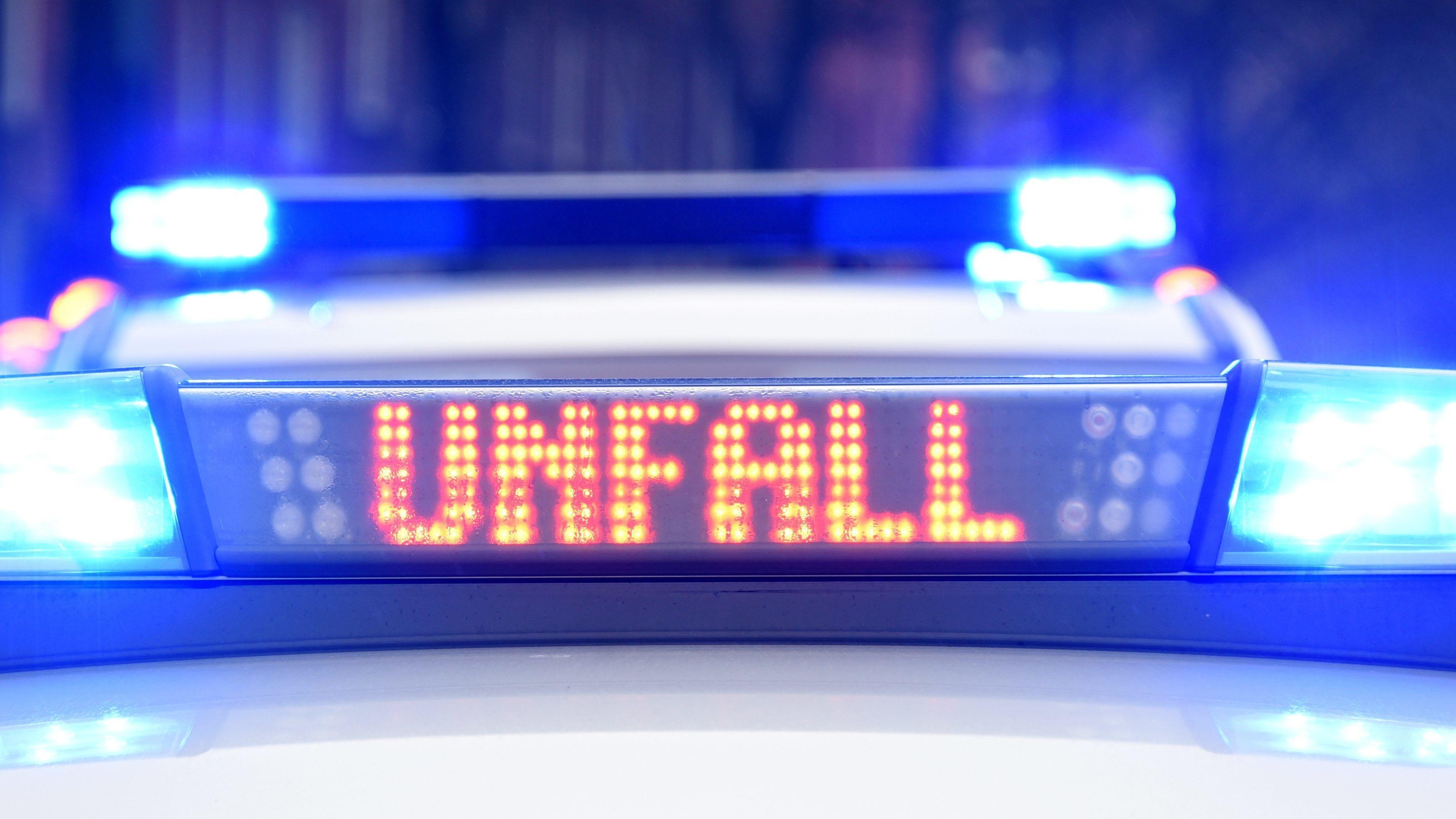 """Blaulicht und der Schriftzug """"Unfall"""" leuchten auf dem Dach eines Polizeiwagens an einer Unfallstelle."""