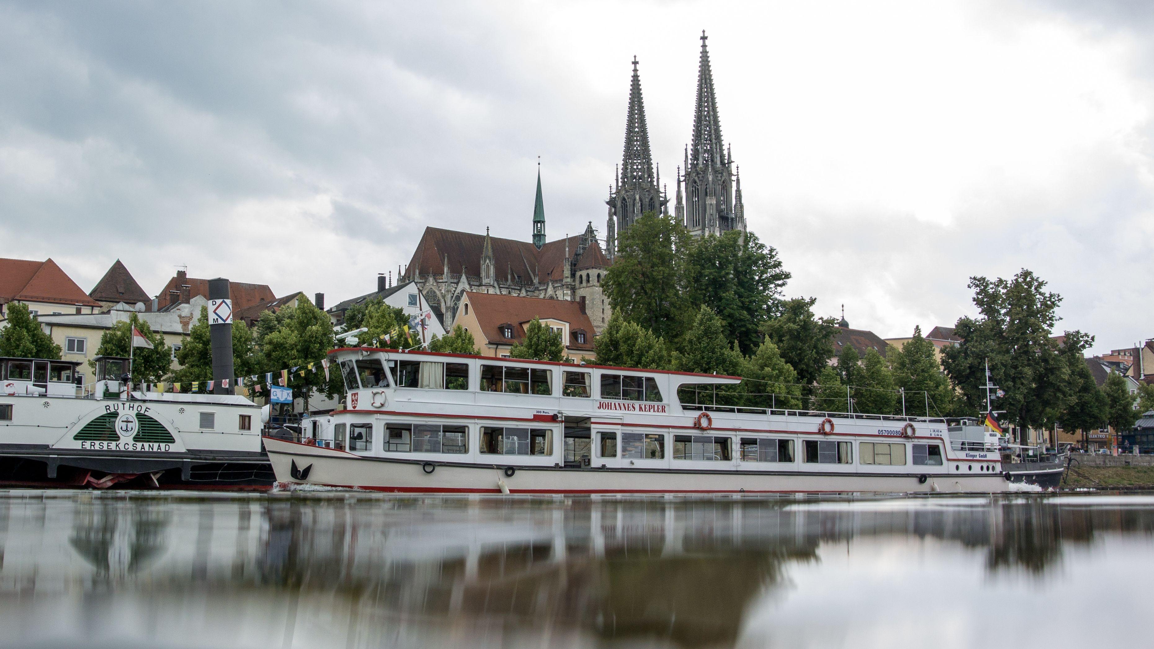 Ein Ausflugsschiff fährt auf der Donau in Regensburg