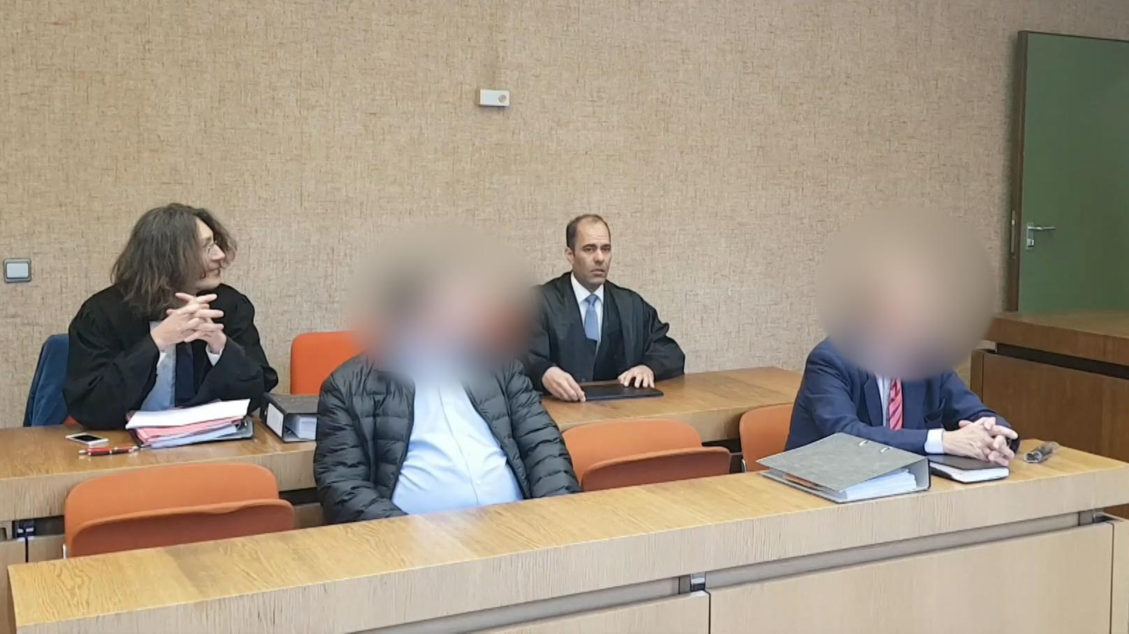 Angeklagte im Gerichtssaal mit Anwälten