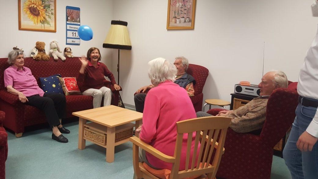 Die Demenzkranken sitzen auf Sofas und werfen sich einen Luftballon zu.