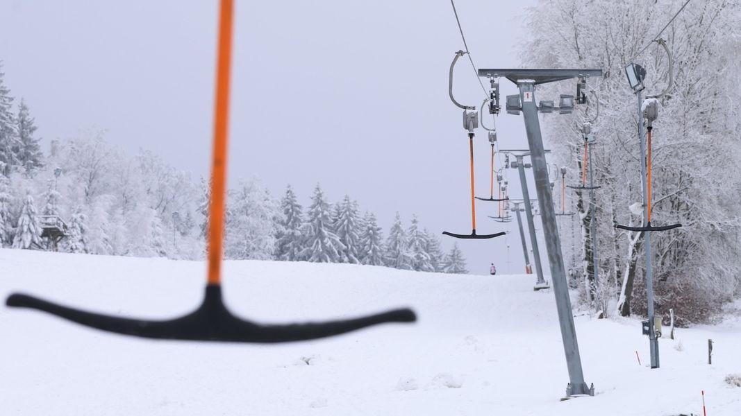 Leere Bügel hängen an einem Skilift.