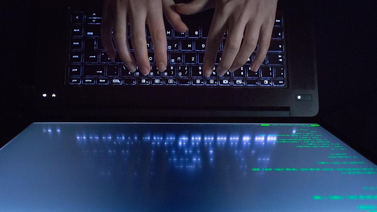 Hände tippen auf einem Laptop - auf dem Bildschirm ist Programmcode zu sehen.