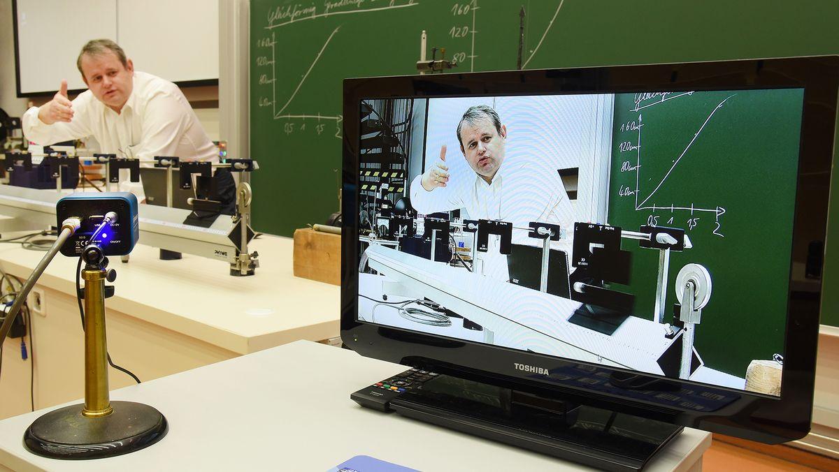 Ein Professor steht vor einer Tafel und überträgt seine Vorlesung in Zeiten von Corona ins Internet