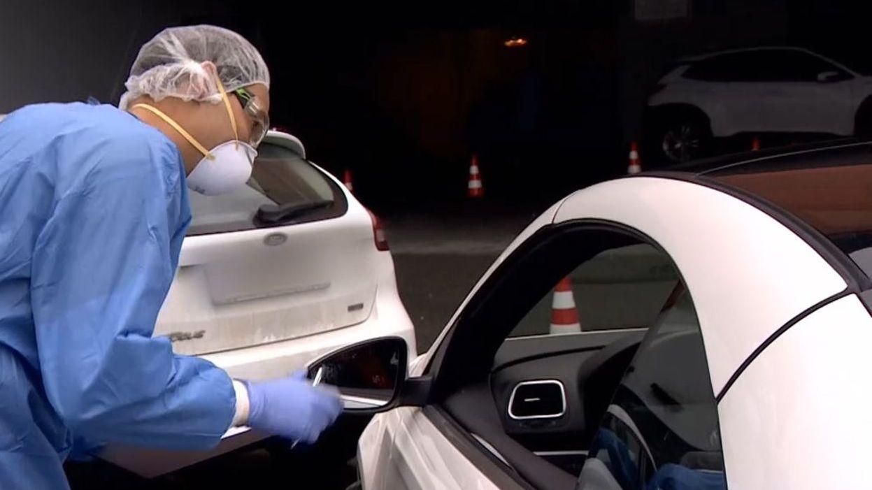 Ein Arzt nimmt an der zentralen Teststelle an der Hofer Freiheitshalle einen Abstrich durch das Fenster eines Autos.