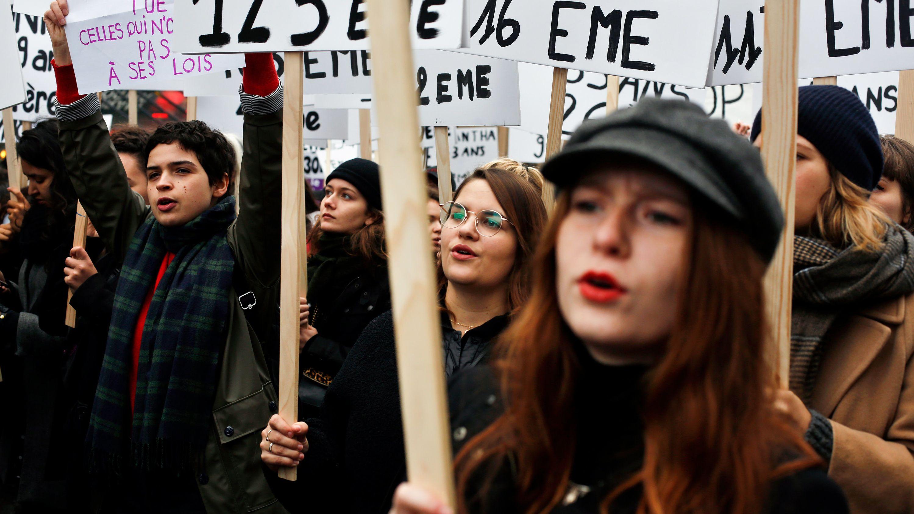 Frauen halten bei einer Demonstration in Paris Plakate, um gegen häusliche Gewalt zu protestieren.