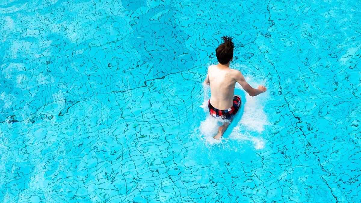 Eine Person spring in einen Pool.