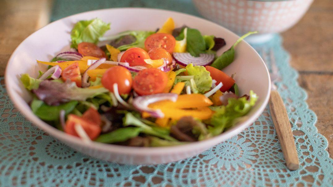 Auf einem gedeckten Tisch steht ein Teller Salat.