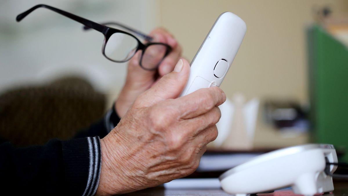 Seniorin hält Telefon in der Hand