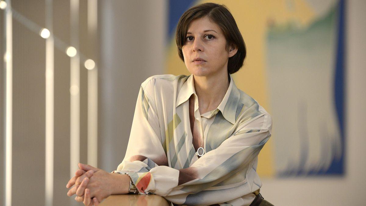 Die Künstlerin Lucy McKenzie steht vor einem Bild ihrer Ausstellung, trägt eine leichte, sanft fallende Bluse, deren Farben mit dem Gemälde im Hintergrund spielen.