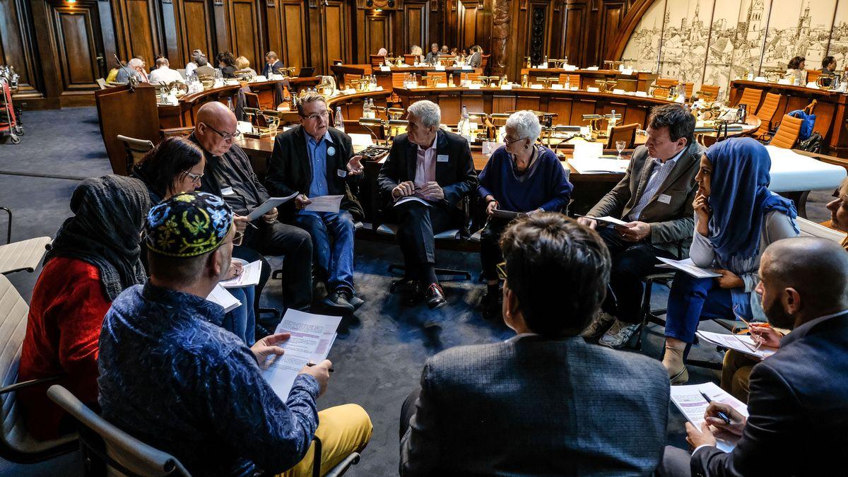 Menschen unterschiedlicher Religionen sitzen in einem Gesprächskreis