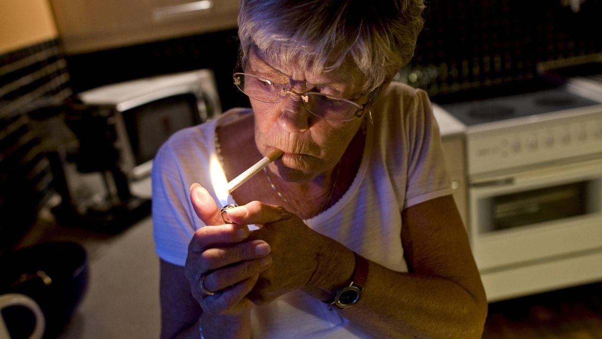 Ältere Frau raucht in der Küche