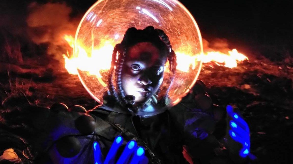Eine weibliche Person Of Colour mit Dreadlocks, den Kopf in einem Raumfahrerhelm, streckt blau behandschuhte Hände nach oben - Hinter ihr lodert in der Dunkelheit eine horizontale Feuersbrunst