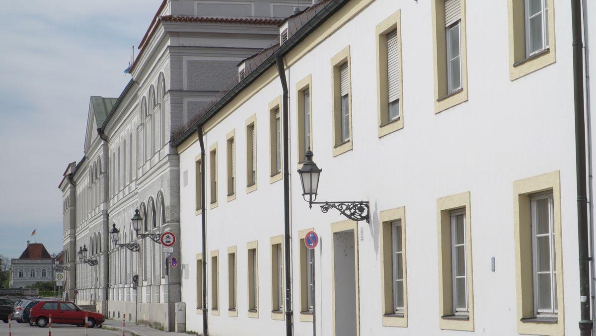 Die Schlossfassade der nördlichsten Bauteile des Schlosses Nymphenburg, im hinteren Bildteil die graue Fassade des älteren Bauteils im Süden, im vorderen Bildteil die weiße Fassade des daran angrenzenden Baus aus den 1960er-Jahren.