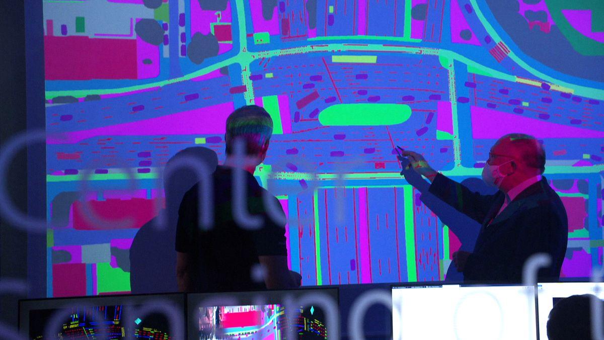 Wissenschaftler des DLR betrachten eine HD-Karte auf einer großen Leinwand