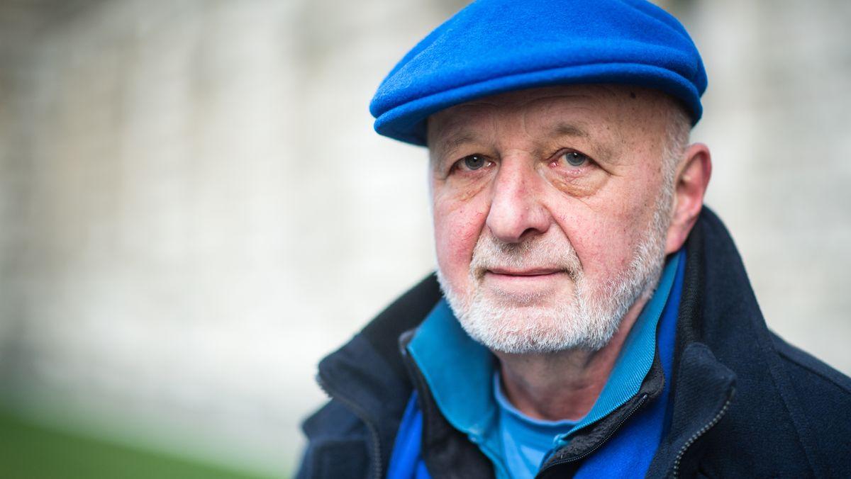 Aktionskünstler Wolfram Kastner blickt, eine blaue Kappe auf dem Kopf, ernst in die Kamera