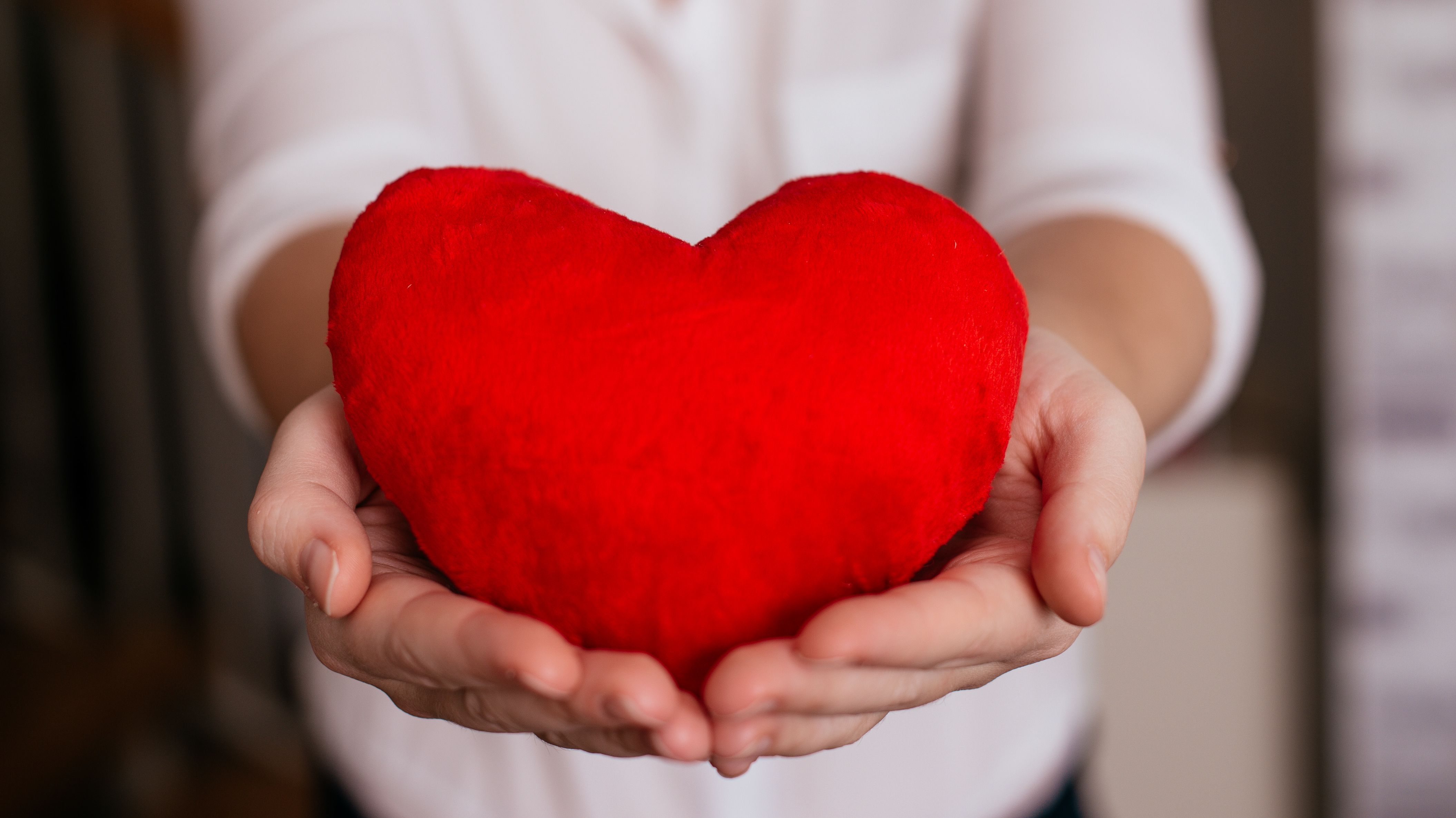 Eine Frau bietet ein Herz aus Stoff mit ihren beiden Händen an.
