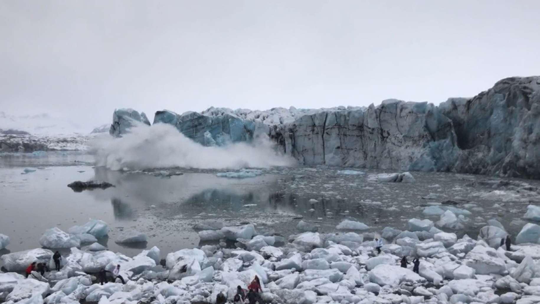 Am Jökulsalon-See stürtzt das Eis eines Gletschers ins Wasser - Touristen bringen sich in Sicherheit