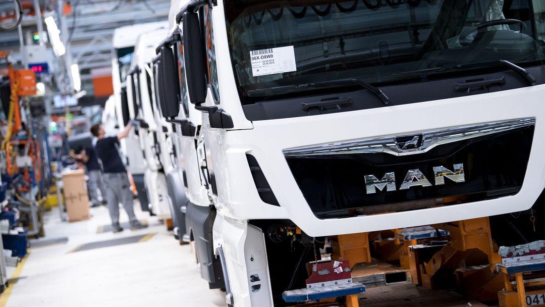 Mitarbeiter von MAN Truck & Bus arbeiten in einer Produktionsstraße