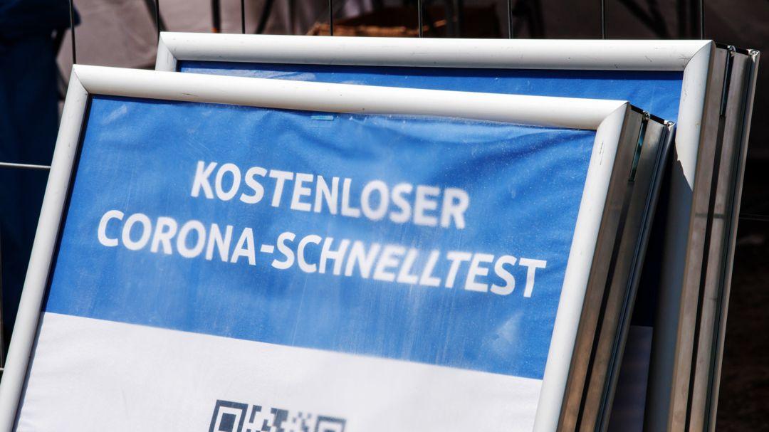 """Ein Schild mit der Aufschrift """"Kostenloser Corona-Schnelltest"""" steht vor einem Testzentrum."""
