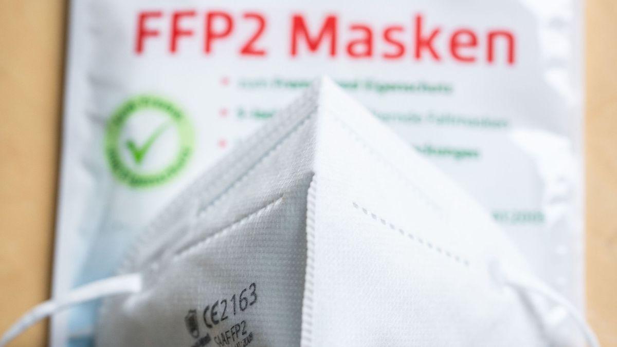 """Eine weiße Maske, dahinter eine Tüte mit der Aufschrift """"FFP2 Masken"""" in roten Buchstaben."""