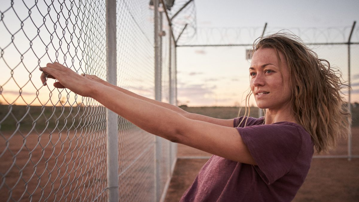 Sofie Werner gespielt von Yvonne Strahovski schaut durch den Stacheldrahtzaun der Einwanderungshaft in die australische Wüste.
