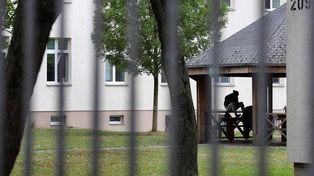 Ein Asylsuchender sitzt vor einem Wohnblock im Ankerzentrum Schweinfurt.