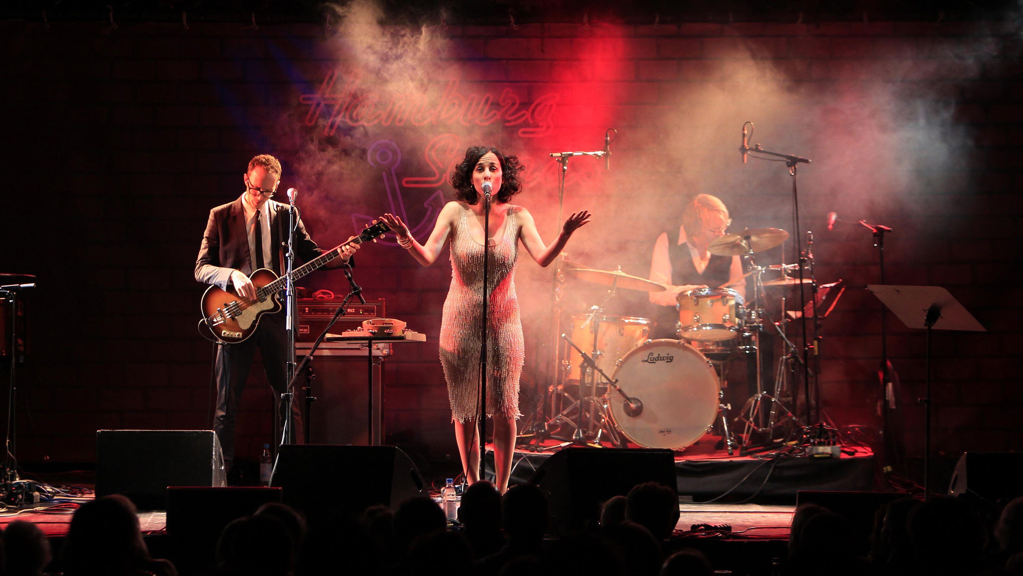 Lisa Bassenge mit Schlagzeuger und Gitarristen auf einer nebligen Bühne