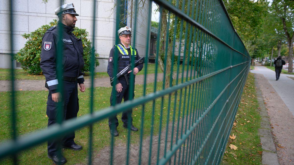Polizisten stehen am Tag nach der Attacke auf einen jüdischen Studenten vor der Hamburger Synagoge hinter dem Zaun vor dem Gebäude und halten Wache.