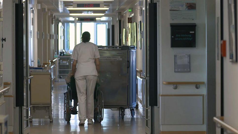 Eine Pflegerin schiebt eine Senioren im Rollstuhl durch den Gang des Krankenhauses.