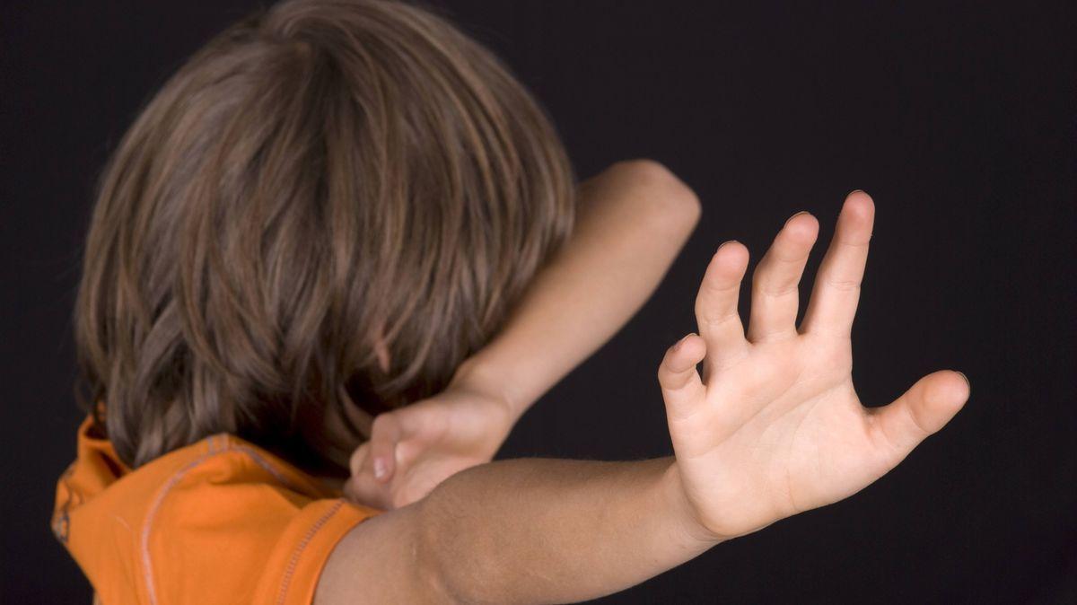 Junge wehrt sich und hält sich die Arme schützend vor das Gesicht