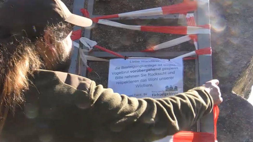 Ranger Andreas Hofmann sperrt die Leiter an einem Felsen mit Absperrband und bringt ein Erklärschild an.