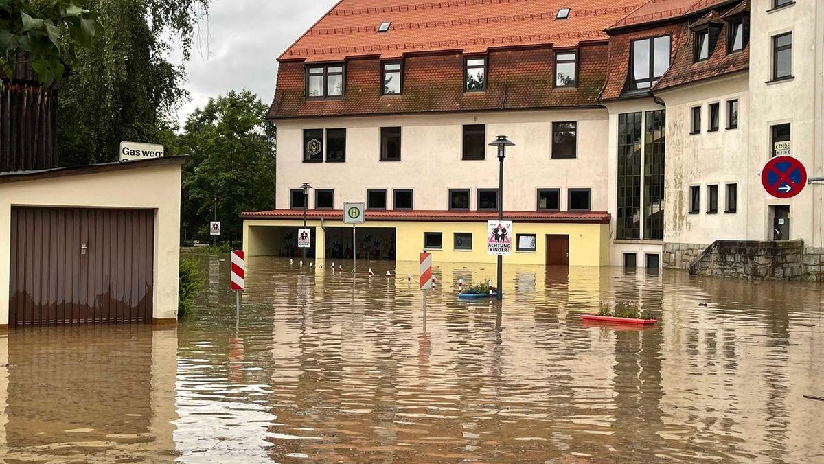 Überschwemmte Straßen vor einem Mehrfamilienhaus