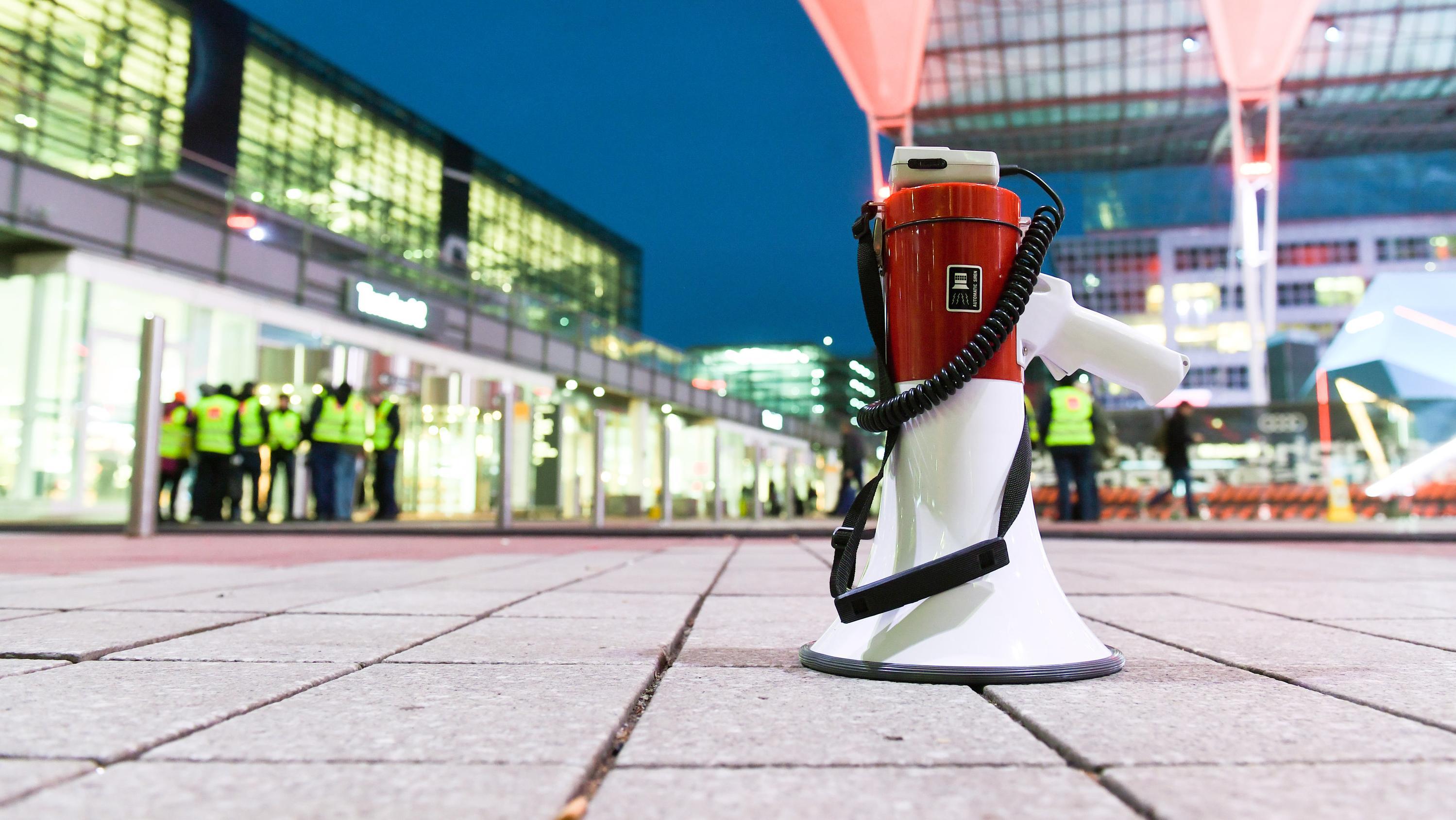 München: Ein Megafon steht am Flughafen auf dem Boden vor dem Terminal 2, vor dem Gebäude haben sich auch Mitarbeiter im Warnstreik versammelt.