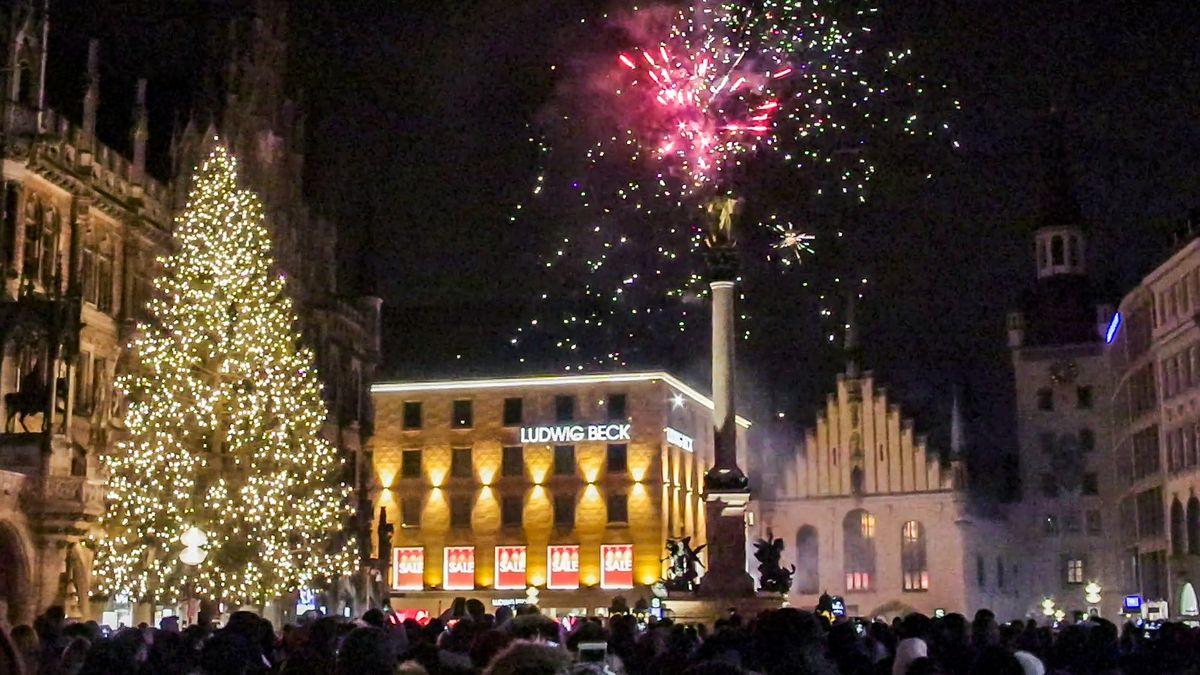 Silvester am Münchner Marienplatz. Feiernde vor Ludwig Beck, daneben der hell erleuchtete Weihnachtsbaum, ein rotleuchtendes Feuerwerk am Himmel.