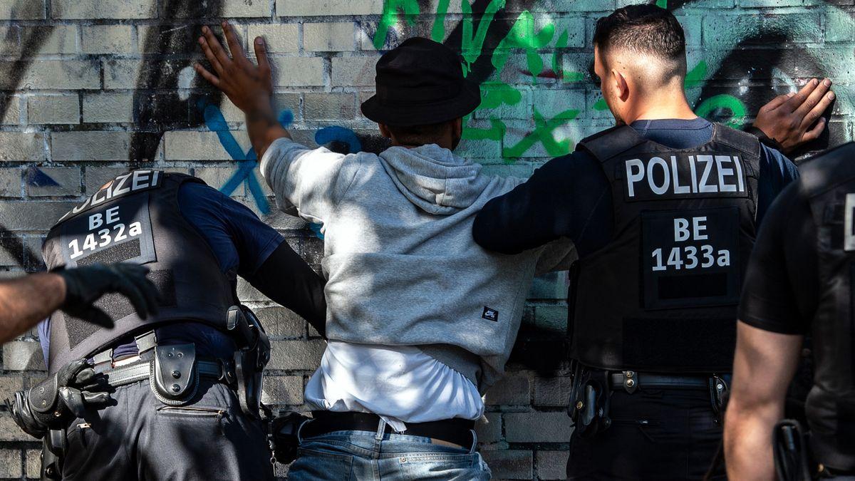 Polizeibeamte kontrollieren in einem Berliner Park einen Mann mit dunkler Hautfarbe als mutmaßlichen Drogendealer.