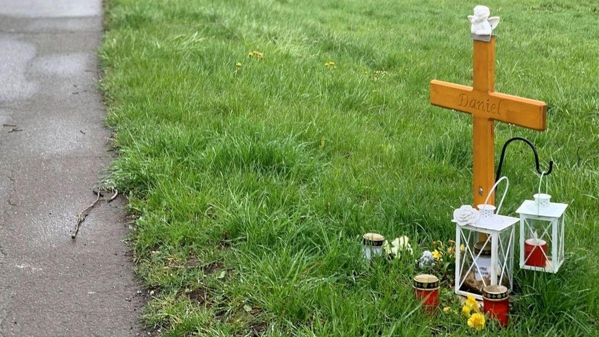Ein Kreuz und Kerzen stehen auf der Wiese