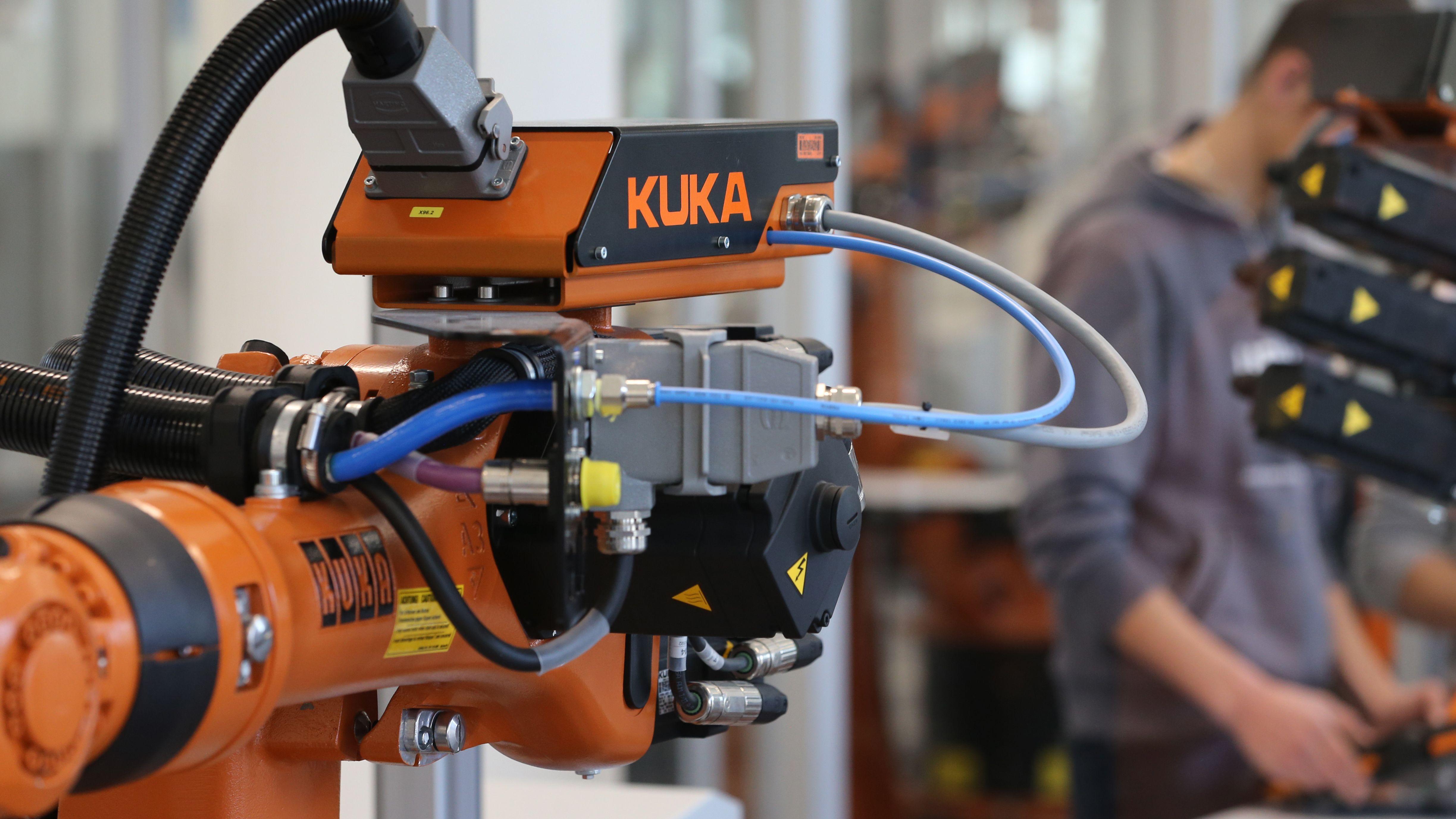 Kunden des Roboterbauers Kuka stehen im Kuka-College an einem Kuka-Roboter.