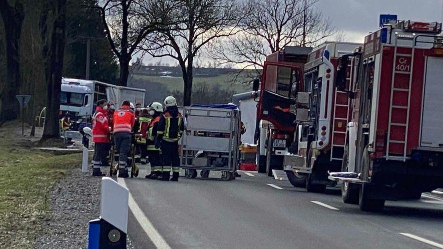Feuerwehrleute stehen auf der gesperrten Straße, dahinter eine Lastwagen.